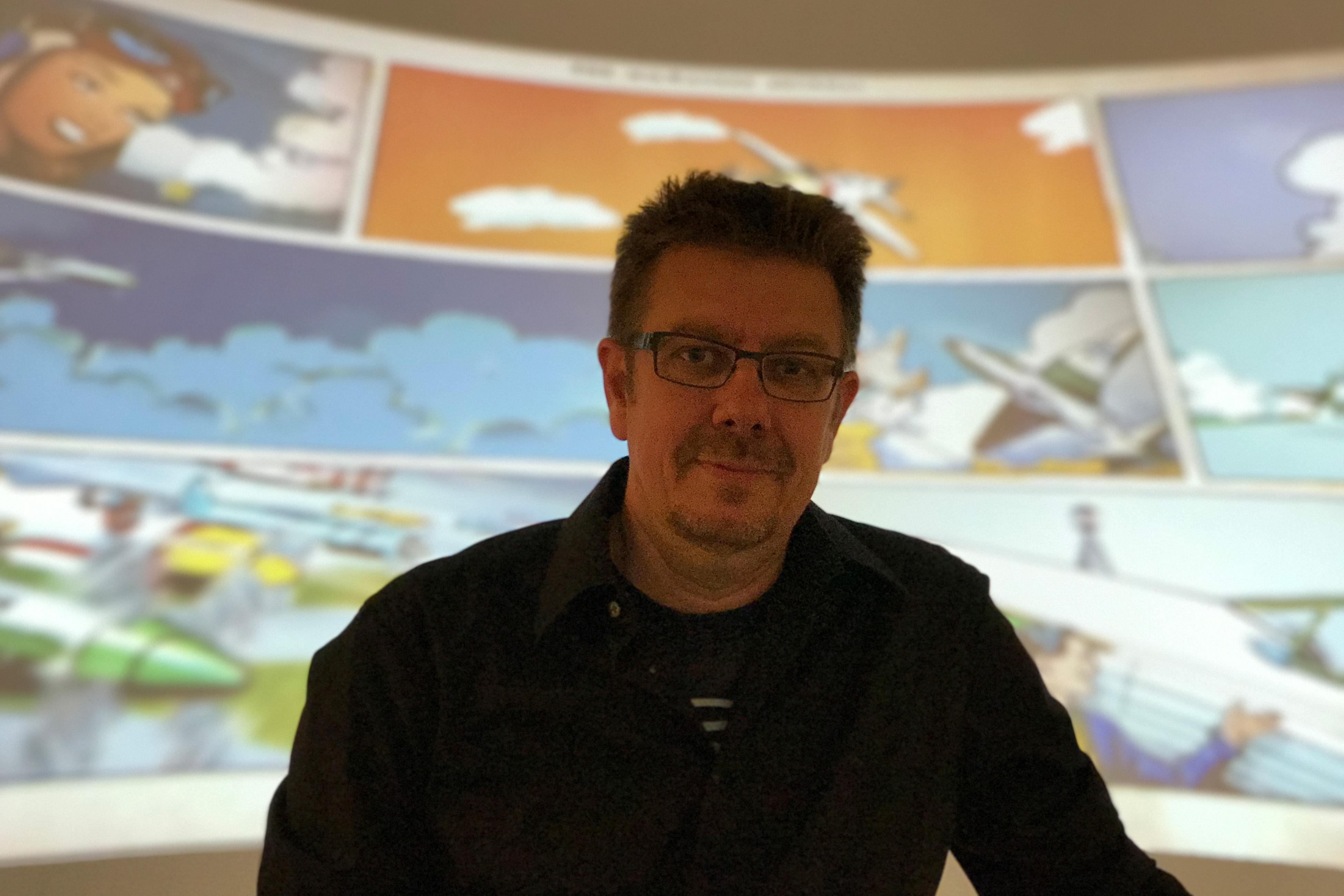 Alexander Braun posiert vor einem Comic-Film, der in der Ausstellung gezeigt wird