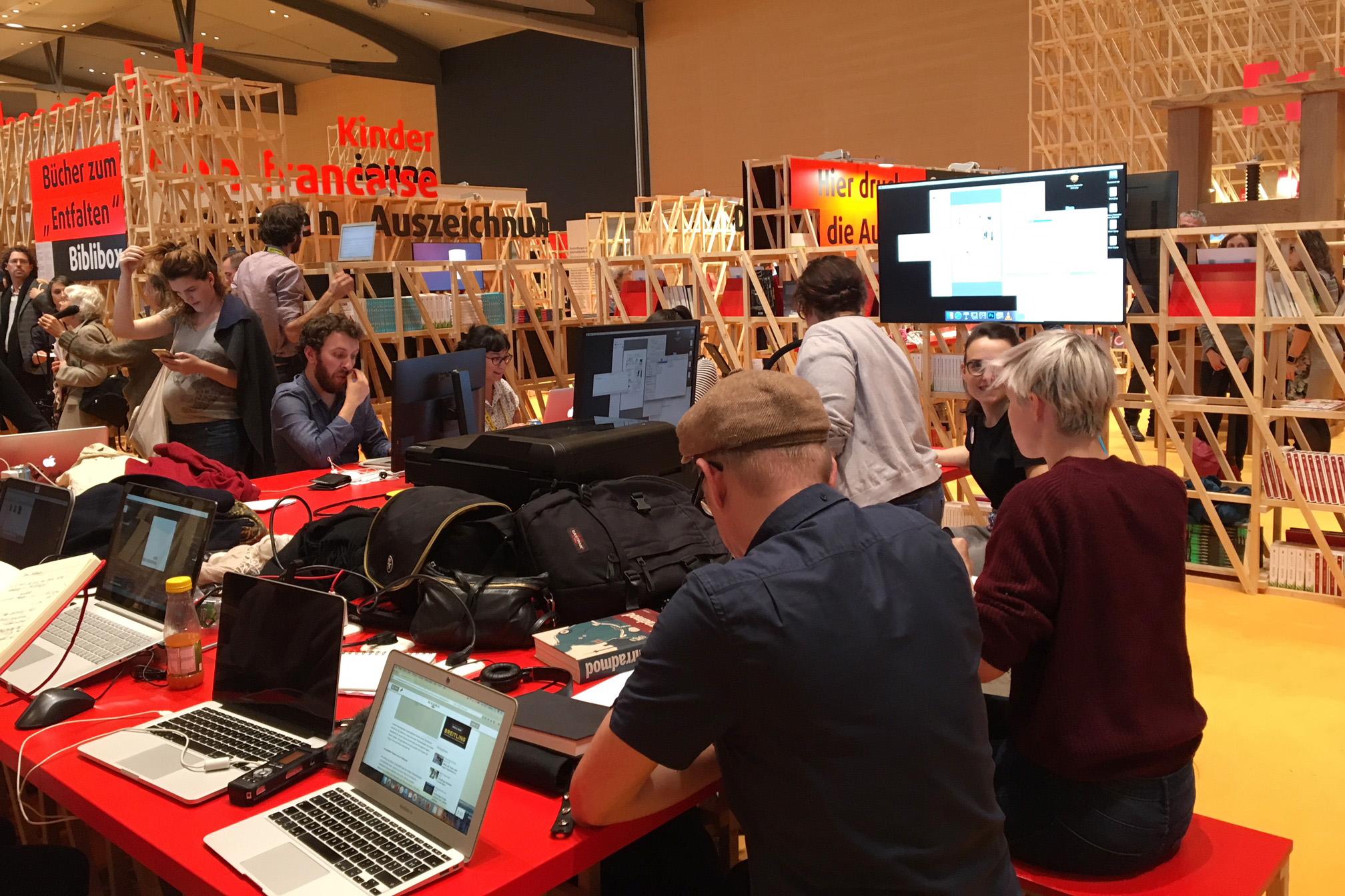 Mehrere Personen sitzen vor Laptops und Monitoren im französischen Pavillon der Buchmesse Frankfurt.