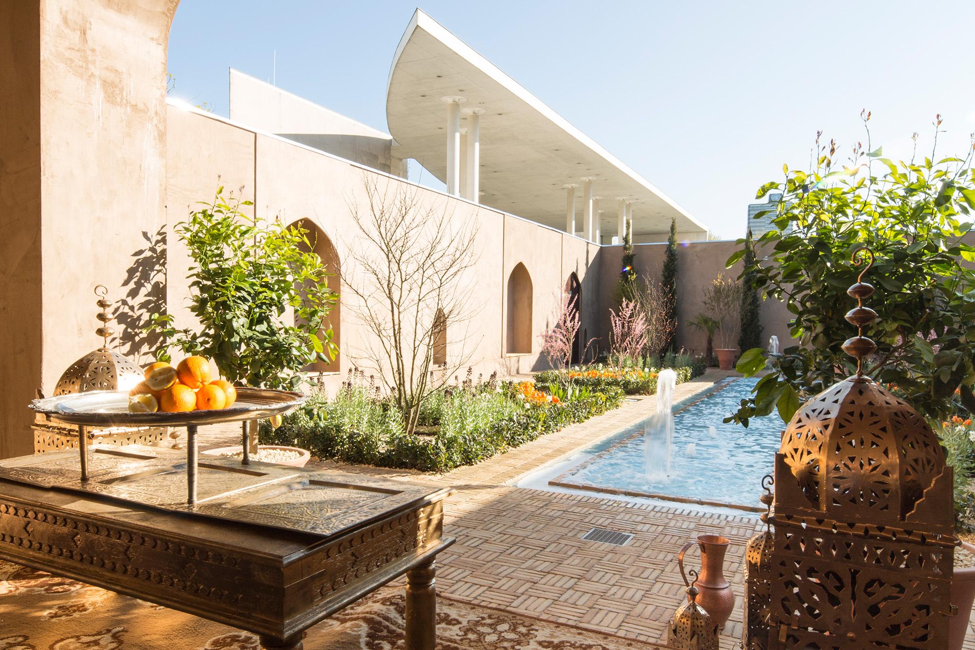 Orangen auf dem Tisch, Wasser, Pflanzen und Museumsgebäude