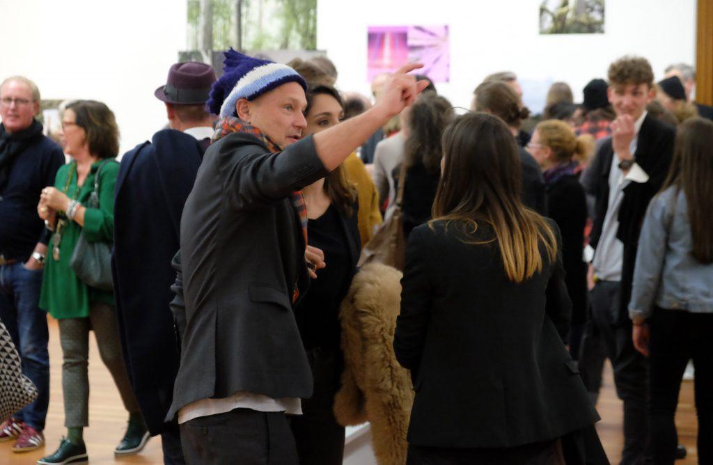 Ausstellungsraum, viele Menschen, Kunstwerke an den Wänden