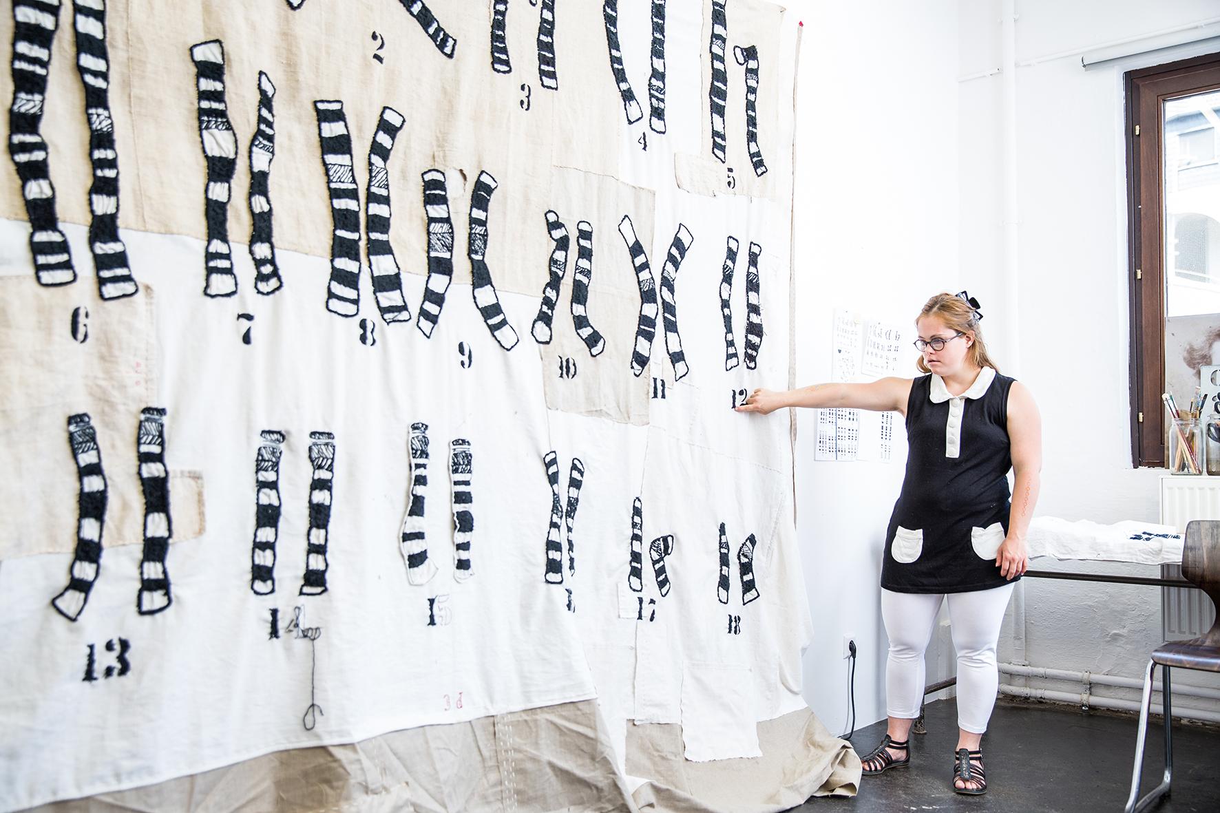 Frau mit Down-Syndrom erläutert den Chromosomen-Wandteppich
