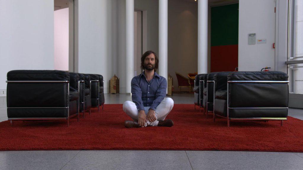 Gregor Schwellenbach auf dem Boden sitzend im Foyer der Bundeskunsthalle