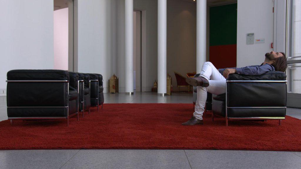 Gregor Schwellenbach liegt in einem der Sessel im Foyer der Bundeskunsthalle
