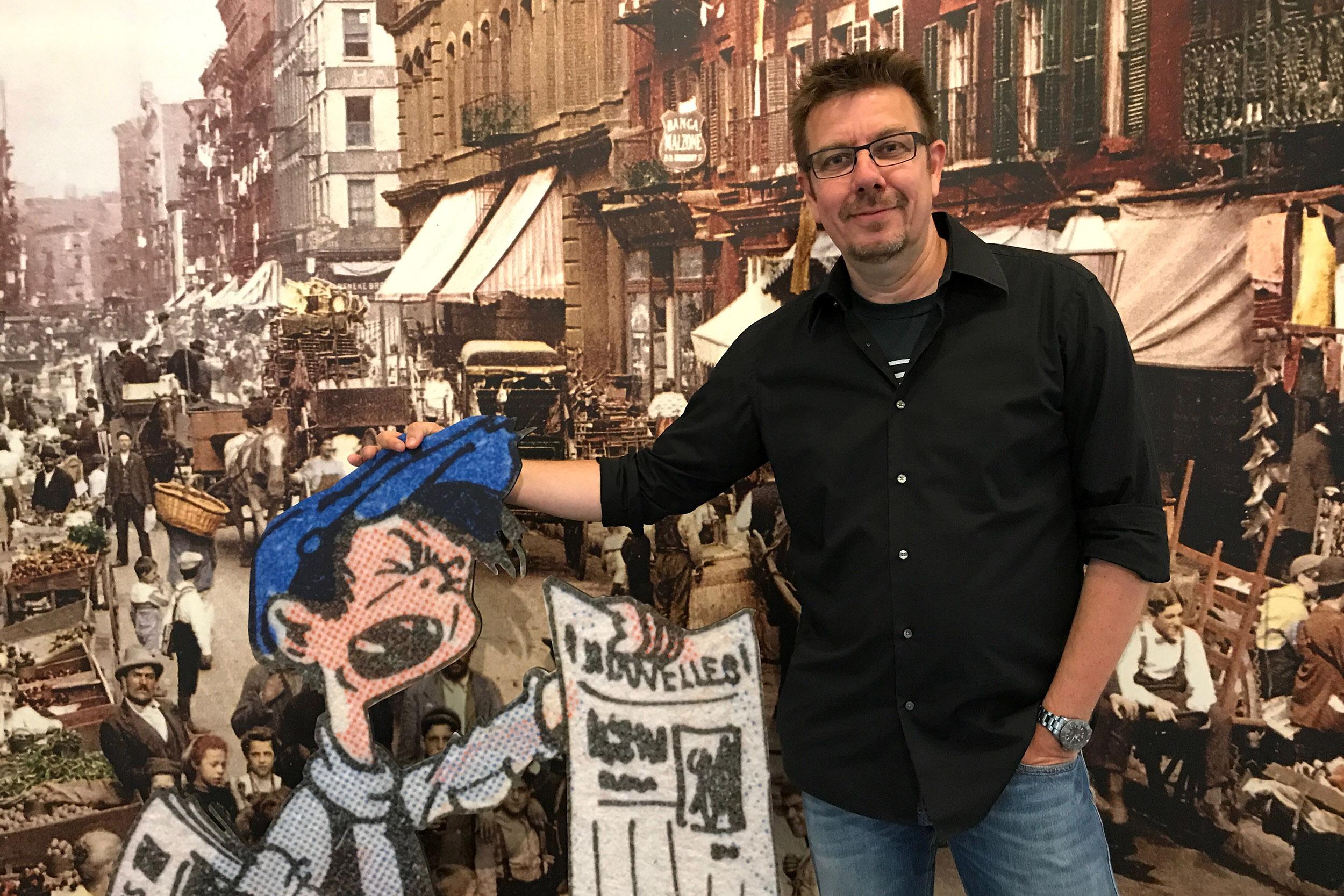 Alexander Braun posiert mit einem Pappaufsteller eines Zeitungsjungen