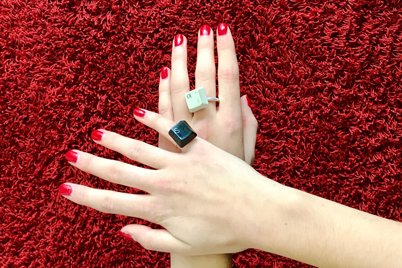 Hände mit alten Tasten, die zu Ringen umfunktioniert wurden
