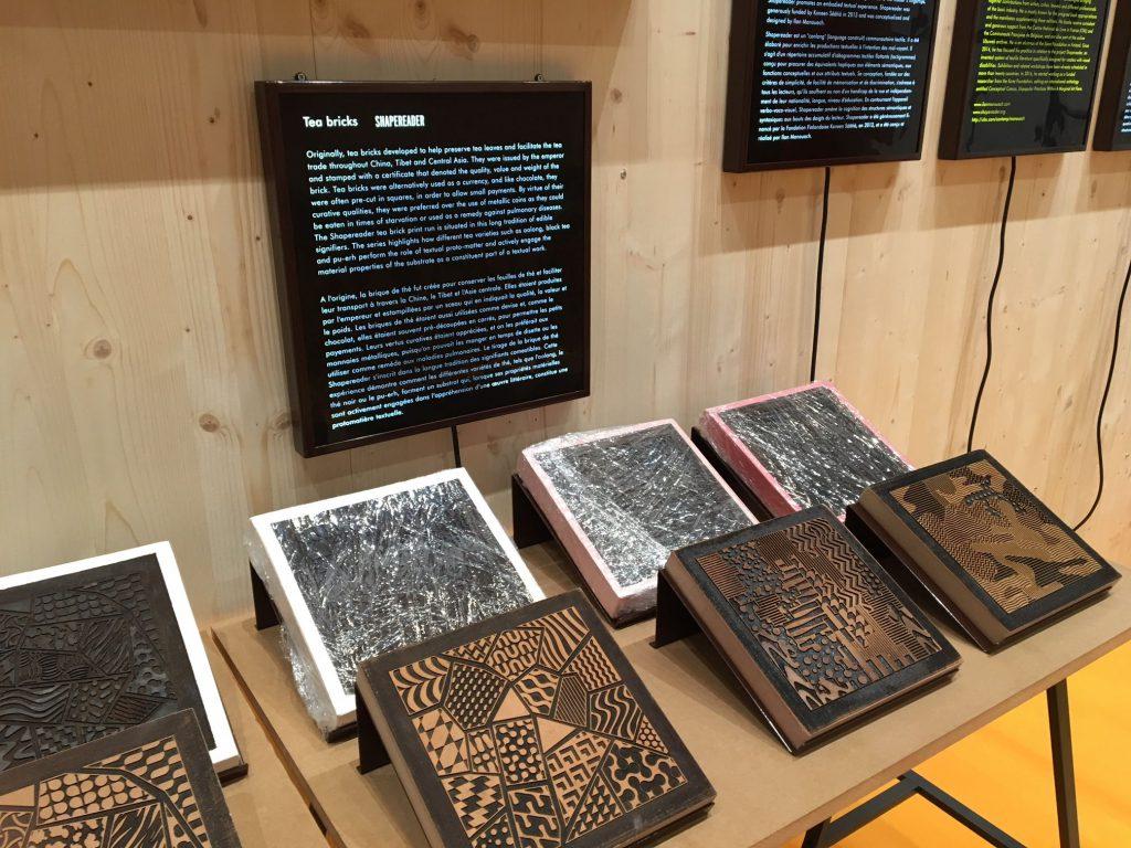 Abgebildet ist das Projekt Shape Reader - Tea bricks. Man sieht quadratische Platten mit gravierten Strukturen. Teeziegel waren gleichzeitig Währung und Nahrung und wurden zum Versand von Teeblättern gedient, waren aber gleichzeitig auch beschriftet und lesbar. Der Künstler Ilan Manouach hat sie übersetzt in taktile Strukturen, die nun auch für Sehbehinderte erfassbar sind.