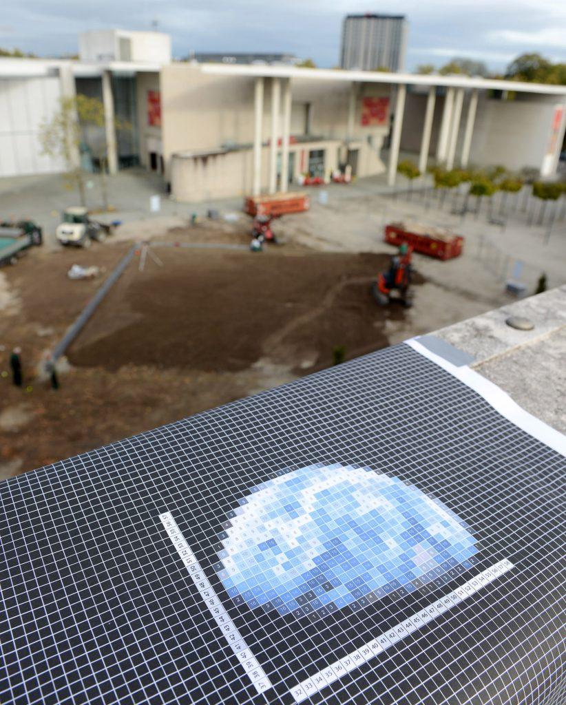 Blick vom Dach der Bundeskunsthalle. Der Bauplan des Kunstwerks im Vordergrund, Bauarbeiten am Boden im Hintergrund.