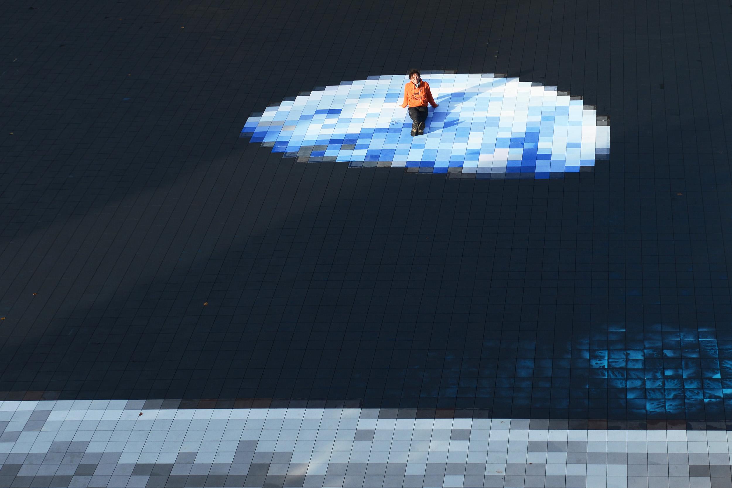 Der Künstler Achim Mohné ruht auf seinem Kunstwerk. Ein großflächiges Mosaik einer Aufnahme der Erde.