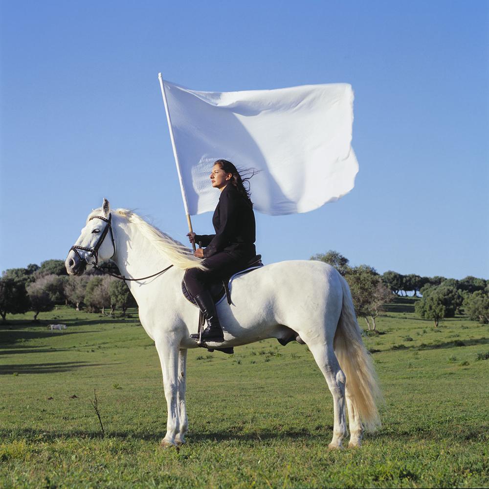 Marina Abramović mit weißer Flagge auf einem weißen Pferd auf grüner Wiese