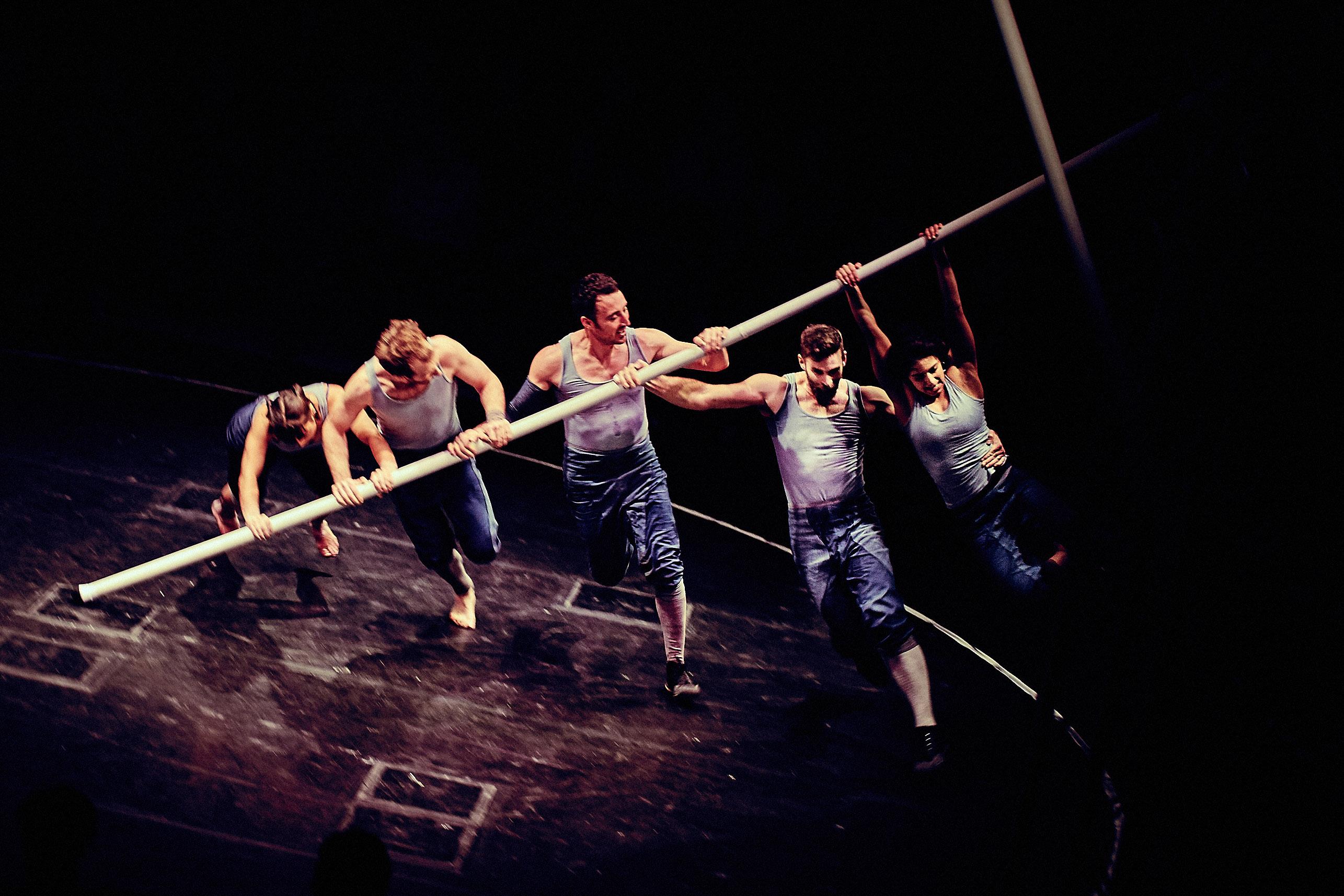 Luftakrobaten auf der Bühne, an einer Stange hängend.