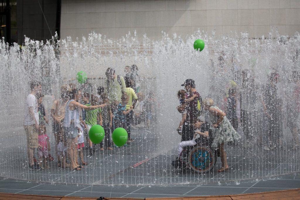 Menschen haben Spaß im Wasserpavillon von Jeppe Hein