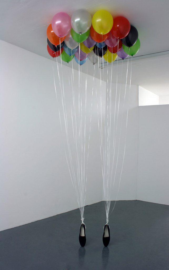 Ballons, die an die Schuhe von Michael Jackson gebunden wurden und unter der Zimmerdecke schweben.