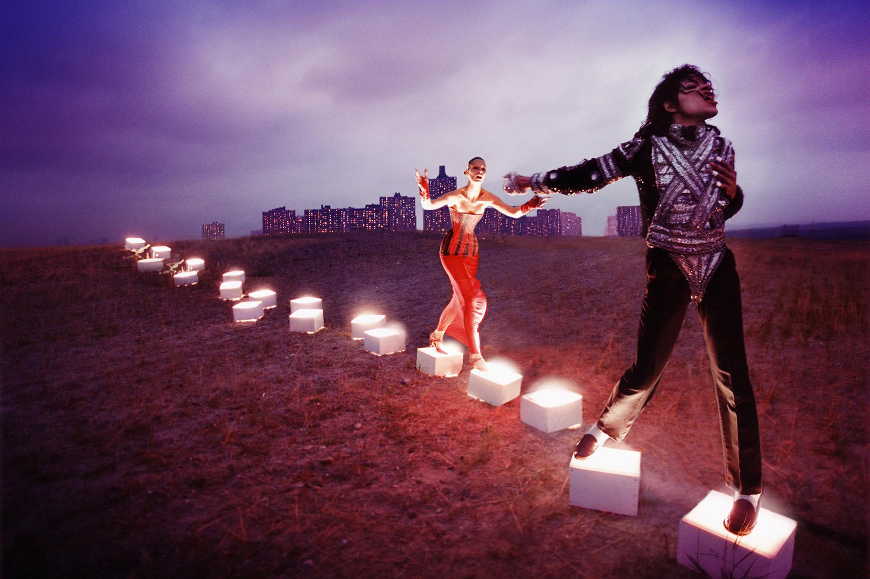 Michael Jackson tanzt und singt während er über erleuchtete Steine wandert, gefolgt von einer Frau