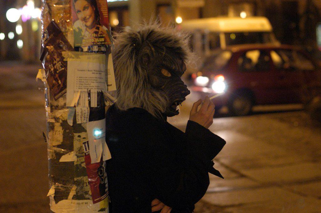 Darsteller mit Wolfsmaske raucht auf der Straße.